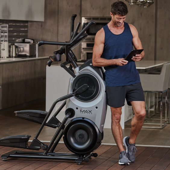 A man standing next to a Bowflex M6