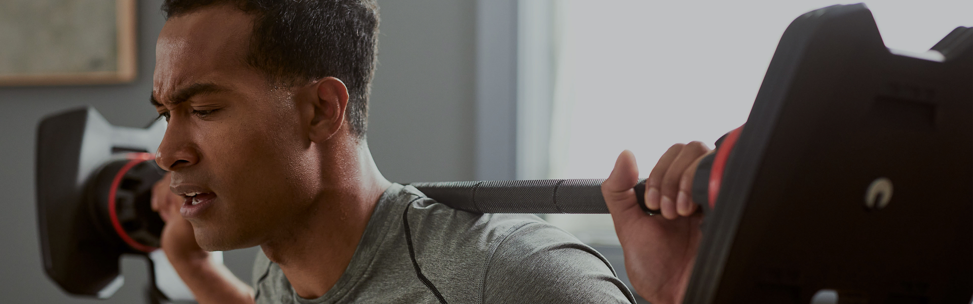 Muscular man working out with the SelectTech Adjustable Barbell