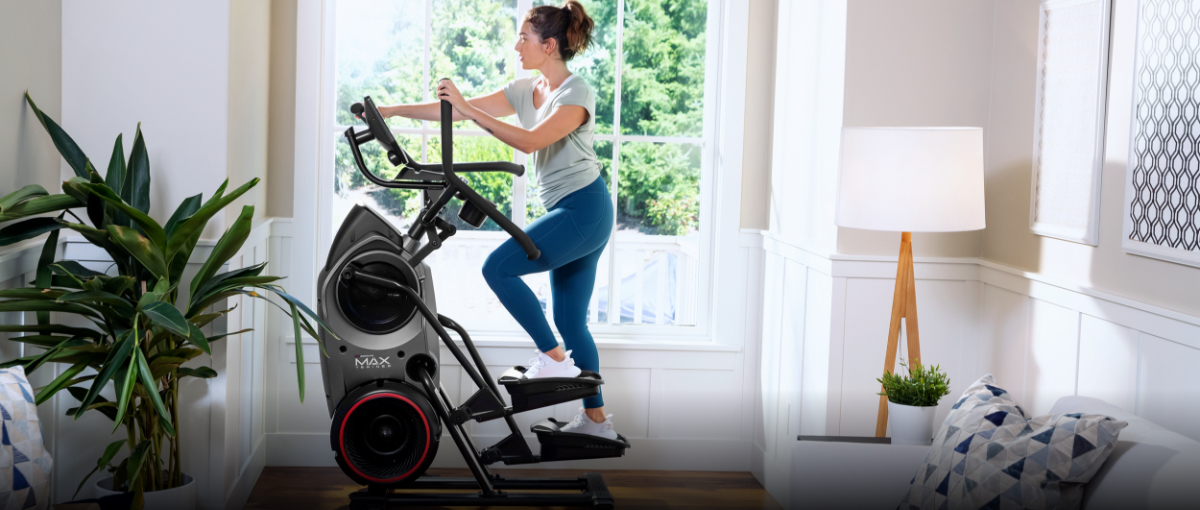 A woman using a Max Trainer compact elliptical located in her home's landing.