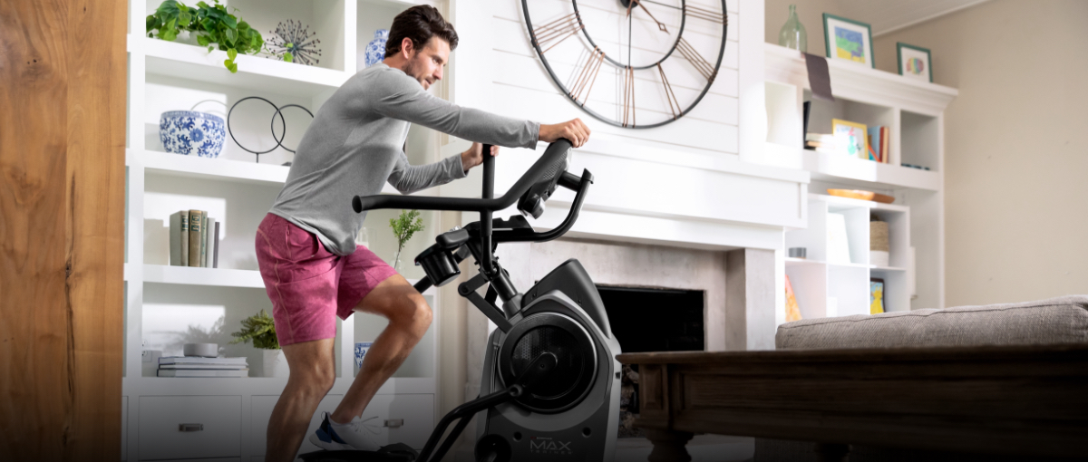A man getting a workout using a Max Trainer compact elliptical located in the corner of a room.