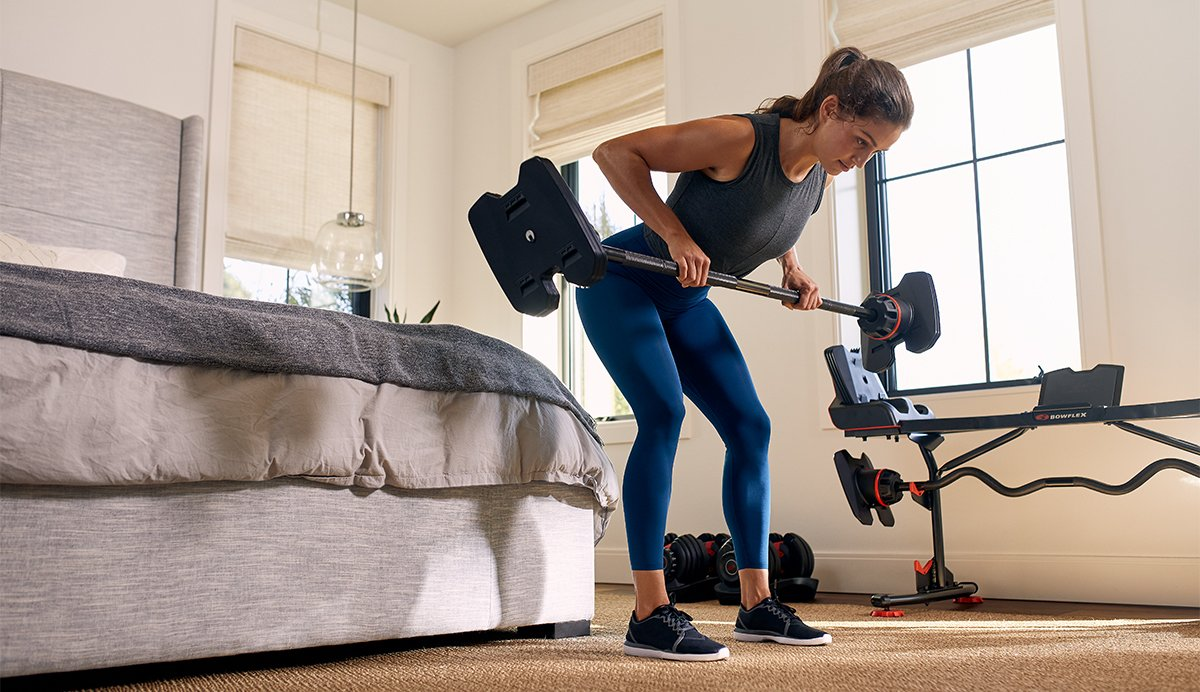 Female doing a bent row exercise with 2080 Barbell in bedroom