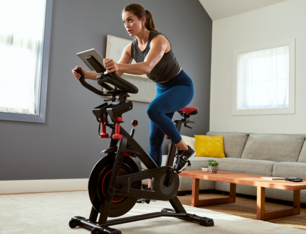 a woman riding a C6 bike in a living room.