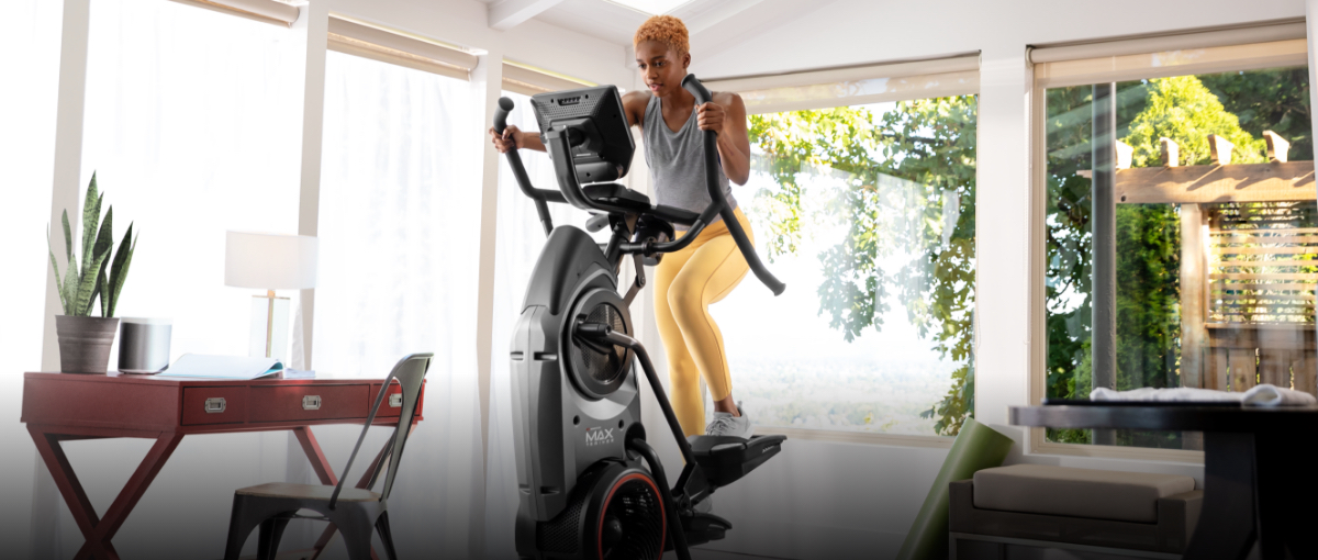 A woman exercising on a Max Trainer compact elliptical from her home office.