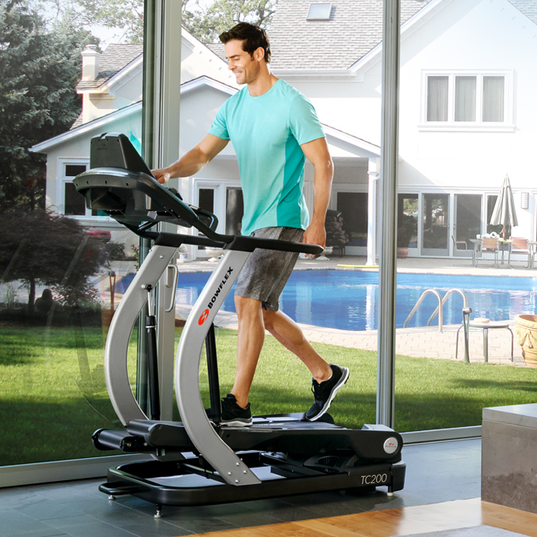 man walking on a treadclimber indoors
