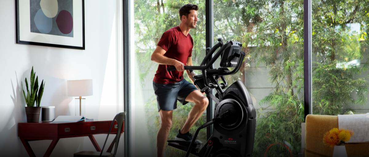 A man exercising on a Max Trainer compact elliptical in his home office.