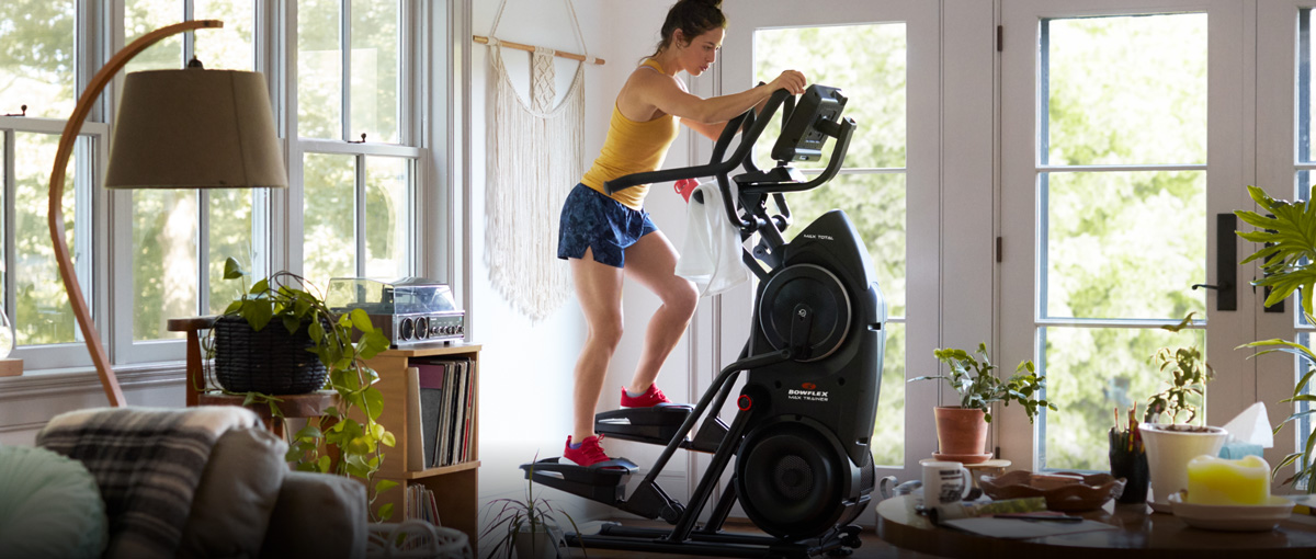 Woman getting a workout with Max Trainer located in the corner of a room