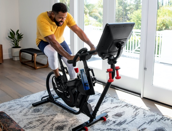 man using the Bowflex VeloCore Bike in a sunny room